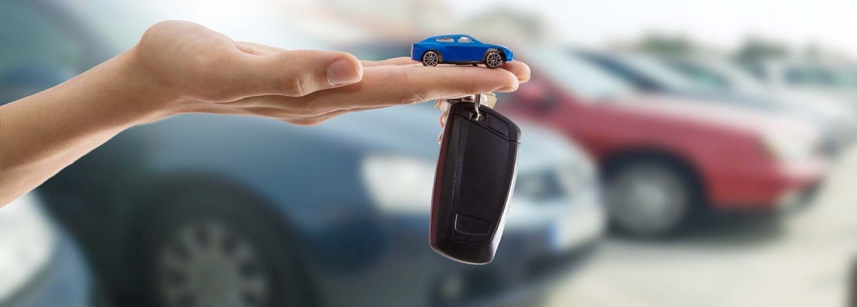 Hand met autosleutel en speelgoedauto met op de achtergrond auto's